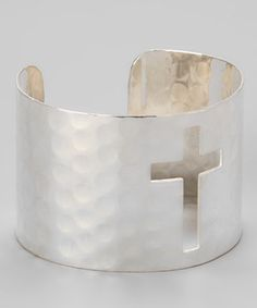 A subtle hammered design details this shiny metallic cuff centered with a cutout of a cross.