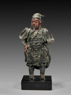 """MING DYNASTY BRONZE GUARDIAN FIGURE Chinese Ming Dynasty bronze figure; of a standing guardian warrior, probably Guandi: in ornate armor, with some original polychrome design; H: 11 1/4""""; wood stand"""