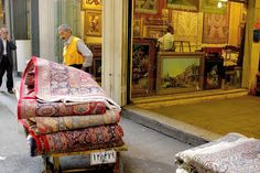 Rug seller in Iran: Hand-made carpets are the most expensive commodity here, with a large district in the bazaar dedicated to their trade. Iran is the world's largest exporter of these artifacts, each piece taking an average of eight months to complete. The art of carpet weaving in Iran dates back thousands of years, to the Achaemenid Persian Empire in the 6th century BC.