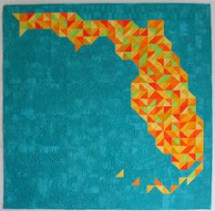 """""""Florida"""" by Linda of #FlourishingPalms has us dreaming of vacations, ocean blues and Florida oranges;). An entry into the Home Machine Quilted category of the 2016 #BloggersQuiltFestival, the quilt measures at 39"""" x 38"""". It was made with lots of 1-1/2"""" x 1-1/2"""" solid fabric half-square triangles and a background of #ModaGrunge Ocean from Moda Fabrics United Notions.   """"I domestic machine quilted Florida on my Janome Sewing Machines 1600P using 50-weight #Aurifil on the top and in the…"""