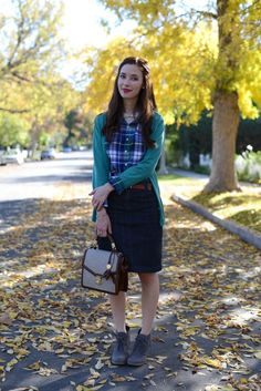 Tucked in plaid button down worn under a non tucked cardigan (rolled sleeves)