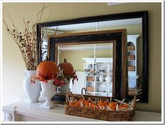 I love this fall mantel - the simplicity of white with the orange of the pumpkins. I also really like the layered mirror look here...
