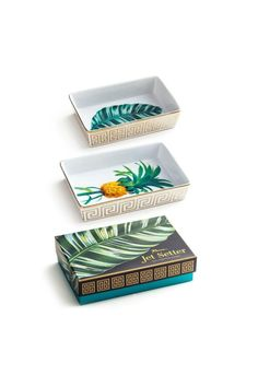 """Welcome to the uber-glam world of Jetsetter a sophisticated and very sexy tropical paradise of black white gold and glittering emerald. Set of two nesting trays in a gift box. Large Tray has a Pineapple motif and the Small Tray has a Palm Leaf.  Dimensions: Large Tray: 8"""" x 5.25"""" Small Tray 6.5"""" x 4""""  Botanical Trays by Rosanna Inc.. Home & Gifts Seattle  Washington"""