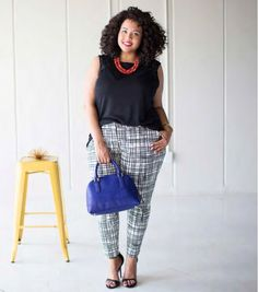 A black top and black and white plaid pant is accessorized with red necklace and royal blue purse.