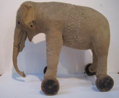Early 1900's Steiff mohair elephant on wooden wheels. Straw stuffed, metal ear button and pull ring for growler. I am so fortunate that I own one like this.