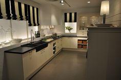 Klassieke, landelijke keuken met twee hoofdkleuren; zwart en gebroken wit. Het werkblad is gemaakt van zwart graniet, de kleur van het werkblad wordt doorgetrokken door de gootsteen.