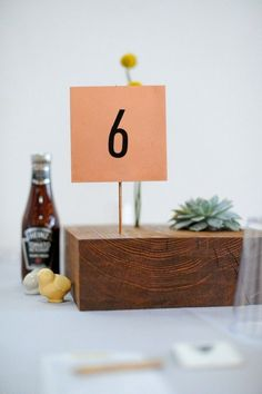 modern wood block centerpiece with succulent and table number