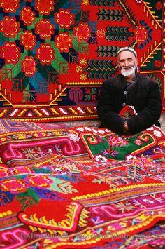 China, Turpan, Xinjiang Province, Uygur or Uyghur Muslim selling colorful carpets in marketplace