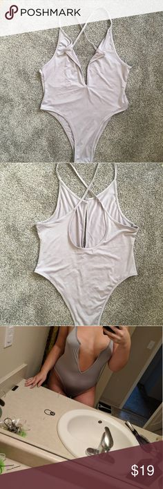 Silky lavender bodysuit, low cut & sexy! Very low plunging neckline if you're in the mood to show some skin! Very comfortable stretchy fabric, you could pair this with so many things, a skater or maxi skirt, high waisted shorts, style it into your wardrobe for a trendy new look. Doesn't have a size on it but I usually wear a medium and this fits! In perfect condition, spaghetti straps that cross over in the back dicloud Other