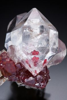 A cluster of double terminated Quartz on red lustrous Cinnabar