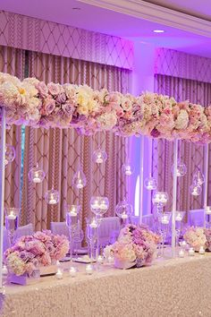 """""""Heavenly"""" is the first word that came to mind when we spotted this incredible pastel arch dripping in candles! #weddingdecor #springwedding"""