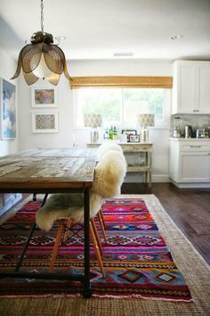 Colourful top area rug is framed with base rug. #layeringarearugs http://www.aftershocksinteriordecorating.com
