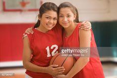 Foto de stock : Multi-ethnic girls hugging in basketball uniforms