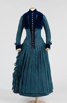 "c 1885 - American, silk, cotton: ""This high style dress made for a girl of about 8-10 years of age is an exact copy of women's clothing, including the bustle silhouette. The only nod to childhood is the short bolero-length vest which was not a typical component of a similar woman's ensemble."""