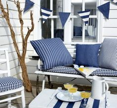 Prestigious Textiles -  Maritime Fabric Collection - Classic chairs and bench with plaid seating pads and striped and plain blue cushions, a...