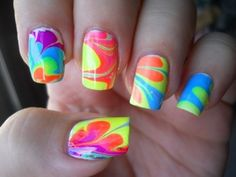 How to make Fun Colorful Nails for this Summer!    You put water in a bowl and drop random colors of nailpolish in it.     Then you stir it with a toothpick and put petroleum jelly on your fingers, so that the nail polish only gets on your nails.     Then you stick your fingers in the bowl.    I just tried this using tape instead of petroleum jelly