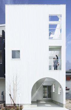 """Residential Architecture: House K by Takeshi Hamada: """"..Beyond the arched entrance of this metal-clad house..is a corner light well surrounded by windows and balconies..Every room inside the three-storey House Kfaces this lightwell, with living and dining rooms on the first floor and bedrooms on the storey above..A staircaseconnectingeach of the floors is positioned behind glass-panel walls at the centre of the house.."""" Abundant natural light, air circulation, very interesting interior insid"""