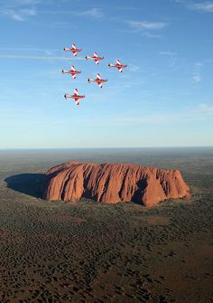 The Roulettes fly in wedge formation over Ayers Rock, Australia. Uluru, also known as Ayers Rock is a large sandstone rock formation in the southern part of the Northern Territory in central Australia. Photo by Department of Defence Ayers Rock Australia, Places Around The World, Around The Worlds, Beautiful World, Beautiful Places, All Nature, Australia Travel, Visit Australia, Wonders Of The World