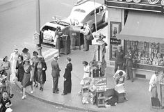 """In this circa late 1930s photo, we're looking regular daily life going on outside the Owl Drug Co. store in the Taft building at the southeast corner of Hollywood and Vine. Most of the people are in hats and the only guy not in a jacket is the post office worker near the top of the picture. I also love that the traffic signal is still the old semaphore style. Apparently, they made a """"bong-clang"""" sound when they changed from Stop to Go—I'd love to have heard it."""