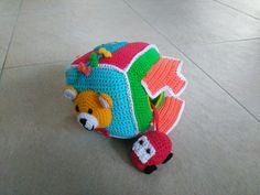 """Leuke gehaakte kubus met rammeltje.  De kubus bevat een holte waar een autootje in opgeborgen kan worden. Thema is :""""Speelgoed"""" Naast de afgebeelde vlakken is er een vlak met een vliegtuig, een zeilboot en een bal. Het patroon is ook te koop. Crochet Toys, Montessori, Crochet Projects, Lana, Dinosaur Stuffed Animal, Crochet Patterns, Baby Shower, Animals, Character"""