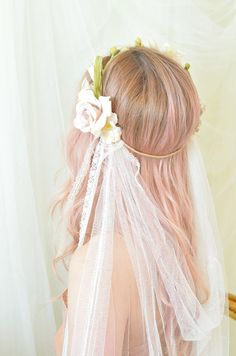 This veil is reminiscent of bygone eras. It features a dainty flower crown of ivory blossoms, floral buds, and a muted mauve pink rose. Their are