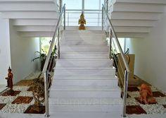 Estatuetas de deuses orientais decoram a imponente escada que conduz ao pavimento superior, revelando que o proprietário está atento a cada pequeno detalhe da decoração da residência.