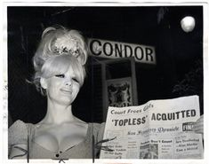Carol Doda proudly displaying the newspaper headline regarding her acquittal outside of the Condor.