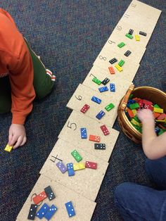 Kindergartners add the two sides of a domino and then put it on the matching plywood square. GREAT for seeing all of the combinations to twelve!