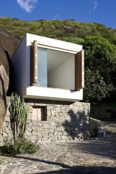 .** contrast natural stone with clean modern, materials; opening up expansive space/window; contrast of smaller window and large opening;   Alan Chu Box House