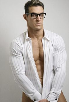 Hunky nerd with glasses wearing a form fitted pin striped long sleeve shirt