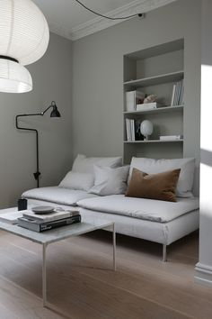 Super stylist updated her IKEA Söderhamn sofa bed with a Bemz cover in a Paler Shade of Grey Panama Cotton   minimal scandinavian inspired living room   matte black wall sconce   perfectly styled book cases   crown mouldings