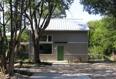 modern studio building with champagne metal siding and green door - austin, tx