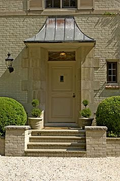 this is gorgeous!  love the texture of the painted brick + patina of the copper portico