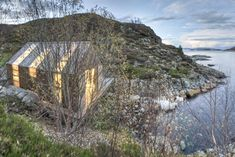 Strips of glazing wrap the walls and roof of a timber waterside summerhouse in Aure, Norway.
