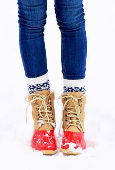 Blue jeans is worn with printed socks, and tan boots.