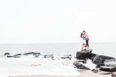 Adventurous Cape May New Jersey Rocky Beach Engagement Session with Crashing Waves By Katelyn James Photography