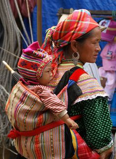 Asia | Portrait of a Hmong mother woman with traditional headscarf carrying her child on a market, Vietnam | Susan Hardman