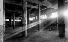 Large warehouse, chair in the middle. It would have less pillars, more empty. Very dark but with a strong beam of light coming through on window right onto the chair.