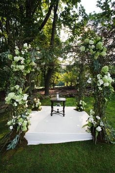 A natural altar is covered with light green and white hydrangeas, branches and dark leaves.