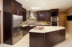 An angled kitchen with a vertical and horizontal glass tile backsplash and an angular island with white countertops.