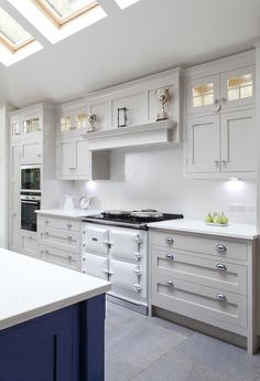 White kitchen with blue kitchen island and kitchen cabinets painted in Farrow & Ball's Elephant's Breath