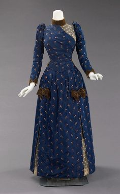 Blue floral-print afternoon dress (front) with olive green velvet trim and lace inserts, American, ca. 1888. Styles of this period were often taken from historical inspiration and covered in various types of trim and lace. Accessories were petite and allowed for the focus on the large elaborate gowns. This period was marked by darker colors, asymmetrical drapery, oversize accessories and elongated forms created by full-length coats.