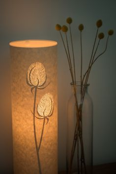 Glowing cylindrical teasel seed head table lamp made from lasercut parchment by Hebden Bridge designer/maker – Hannah Nunn. We ship worldwide from our website www.hannahnunn.co.uk