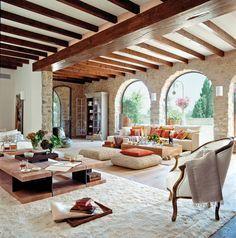 Salón rústico con paredes de piedra y ventanas en arco