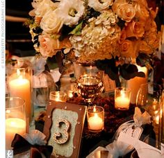 Vintage-inspired glass vases, set on a wooden box of moss, overflowed with white and blush hydrangeas, roses, ranunculus, orchids, and Manzanita branches. Votives in varying sizes flickered throughout the reception.