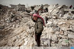 SYRIA, ALEPPO: A Syrian man reacts while standing on the rubble of his house while others look for survivors and bodies in the Tariq al-Bab district of the northern city of Aleppo on February 23, 2013. Three surface-to-surface missiles fired by Syrian regime forces in Aleppos Tariq al-Bab district have left 58 people dead, among them 36 children, the Syrian Observatory for Human Rights said on February 24. AFP PHOTO/PABLO TOSCO