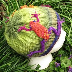 "A beanie in three sizes featuring a grass pattern with frogs jumping through. The beanie is knitted in the round, and the frogs are knitted separately and sewn onto the hat. Instructions are given for a small and large frog. Make as many of either size as you want for your beanie. The small frog is a good fit for the 18"" beanie."