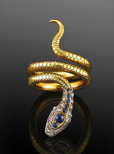 Victorian sapphire and diamond coiled Snake Ring, a finely scaled yellow gold coil forms the tail and body of a snake with a jeweled sapphire and diamond head set in silver top yellow gold.