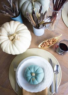 Fall table with painted pumpkins, feathers, and cattails