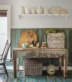 A salvaged worktable provides this kitchen's prep surface. The owner collects pig-shaped cutting boards and snagged this little guy along with the two round ones at a local antiques shop. The breadbox houses the silverware.